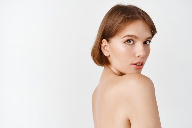 Skin care beauty. beautiful woman standing with naked shoulders, playfully looking  with natural beautiful face, no makeup and nourished healthy facial skin, white wall