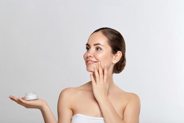 スキンケア。美容コンセプト。化粧クリームを保持している若い女性。ヌードメイクのやわらかい肌モデル。保湿クリームを保持し、自分の顔に触れる女性の肖像画。皮膚の保護と皮膚科。