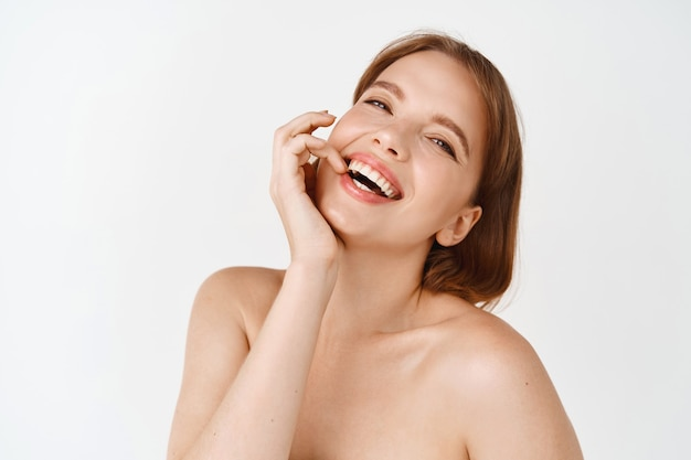 Skin care beauty. natural girl with light make-up, laughing and smiling with smooth hydrated skin, healthy face and teeth, standing with naked shoulders against white wall