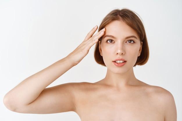 스킨 케어 뷰티. 벌거 벗은 어깨를 가진 자연 소녀, 화장하지 않은 얼굴을 만지고 있습니다. 여성 화장품의 개념