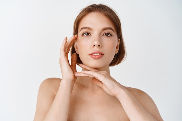Skin care and beauty. natural young woman standing naked, touching glowing face. girl showing skincare product effect, clean fresh skin without blemishes, white wall