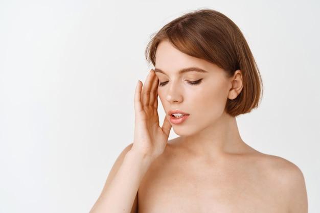 스킨 케어 뷰티. 관능적 인 젊은 여성, 벌거 벗은 어깨, 화장하지 않은 자연스러운 아름다운 얼굴을 옆으로보고 수분 및 해독 효과를 위해 피부 관리 제품에 영양을 공급하고 적용하십시오.