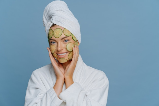 Skin care and beauty treatment concept. happy relaxed young female model applies cucumber slices to nourish skin keeps hands on face dressed in white dressing gown and wrapped towel on head.