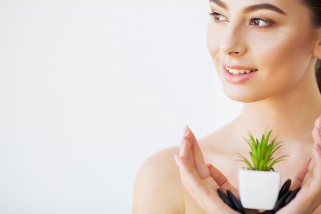Уход за кожей. красота женское лицо с здоровой кожей и зеленым растением