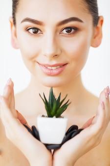 スキンケア。健康な肌と緑の植物を持つ美女の顔。