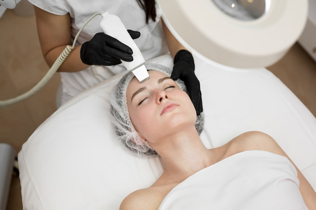 スキンケア。超音波キャビテーション顔の皮をむく美しい女性のクローズアップ。超音波皮膚洗浄手順。美容トリートメント。美容学。美容スパサロン。