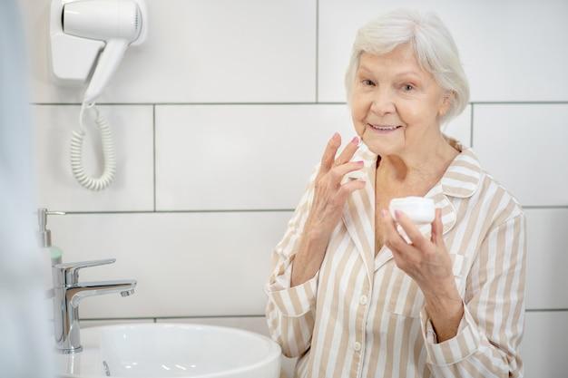 スキンケア。手にクリームの瓶を持つ女性の写真を閉じる