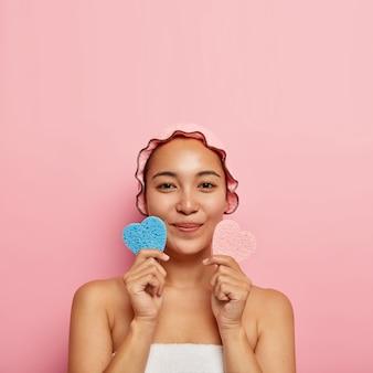 스킨 케어 개념. 아름답고 만족스러운 한국 소녀는 분홍색과 파란색 화장품 스폰지를 심장 모양으로 잡고, 얼굴을 청소하고, 모공을 제거하고, 상쾌 해 보이고, 분홍색 샤워 캡, 흰색 수건을 착용합니다.