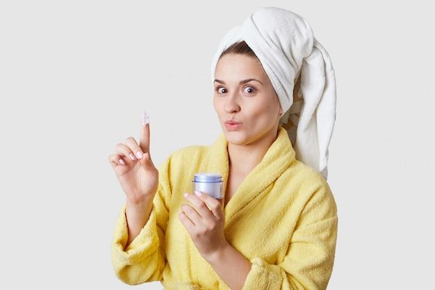 スキンケアのコンセプトです。美しい若い女性は化粧品のクリームを保持し、うれしそうな驚きの表情、白いスタジオの壁に分離された黄色のバスローブを着ています。顔の治療。肌の水分