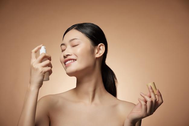 Концепция ухода за кожей - очаровательная молодая азиатская женщина, держащая спрей и лосьон для бутылки с идеальным макияжем, фотокомпозиция брюнетки