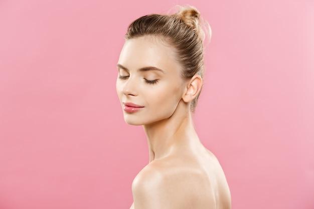 피부 관리 개념-갈색 머리 여자의 완벽한 메이크업 사진 조성으로 매력적인 젊은 백인 여자. 복사 공간와 분홍색 배경에 고립.