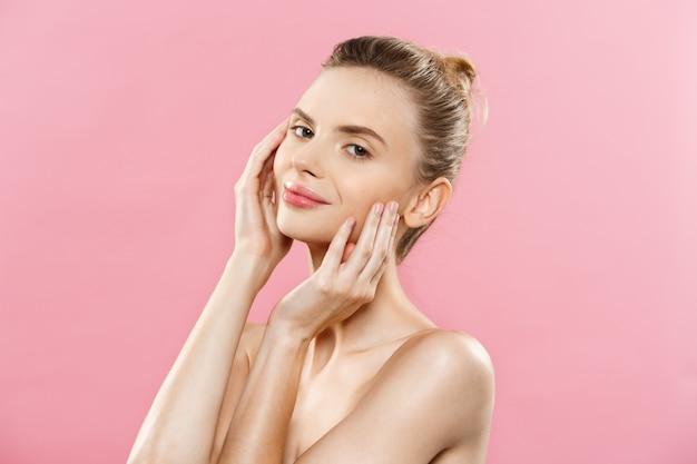 スキンケアコンセプト - 魅力的な若い白人の女性と完璧なメイクアップ写真の組成ブルネットの女の子。コピースペースとピンクの背景に隔離されています。