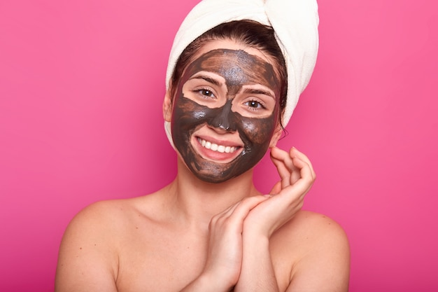 Skin care concept. pleased young woman with toothy smile, has cocholate facial mask, isolated on pink, has natural beauty, wears white towel and has nacked shoulders, keeps hands near face.