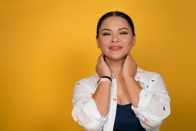 スキンケアのコンセプト。きれいな女性が手で首に触れて微笑む。左側のスペースをコピーします。黄色の背景にスタジオでポーズをとって幸せな中年のアジアの女性。