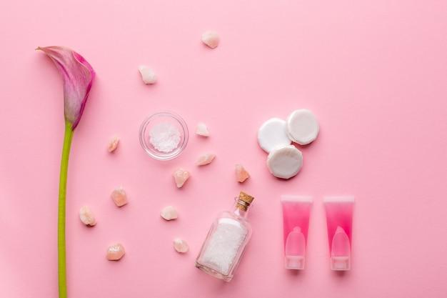 피부 관리 개념. 핑크 파스텔 배경에 바다 소금, 비누, 미셀 물, 칼라 백합 꽃