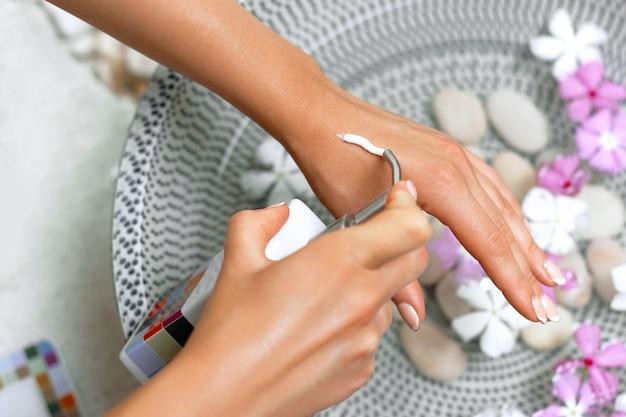 스킨 케어 개념. sp. 핸드 크림, 그녀의 손에 로션 아름 다운 여자. 부드러운 피부에 화장품 크림을 적용하는 천연 매니큐어와 근접 촬영. 뷰티 컨셉