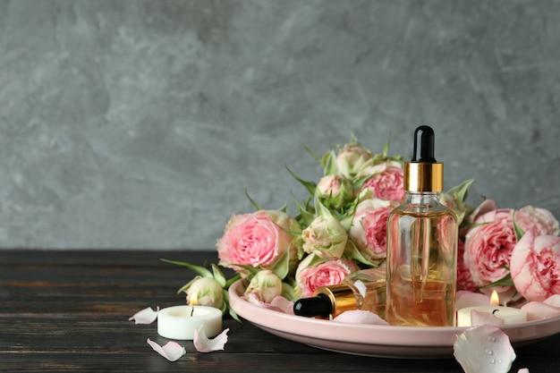 Концепция ухода за кожей с эфирным розовым маслом на фоне серой текстуры