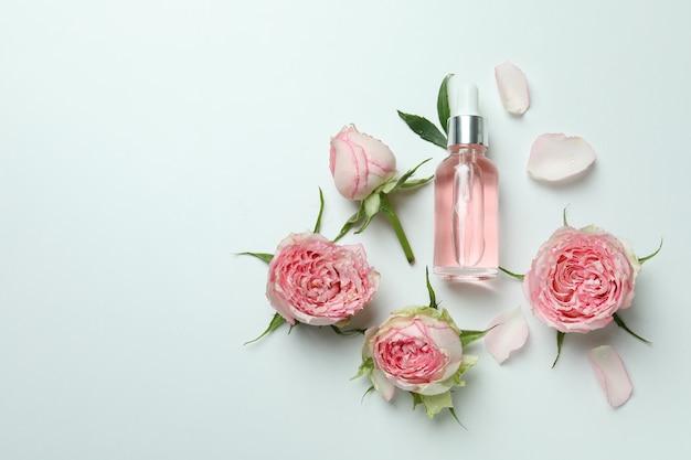 Концепция ухода за кожей с эфирным розовым маслом и розами на белом