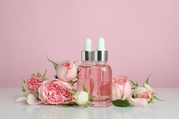 Концепция ухода за кожей с эфирным розовым маслом на розовом