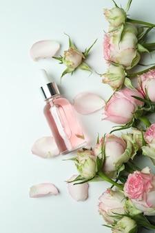 Концепция ухода за кожей с эфирным розовым маслом на белом, вид сверху