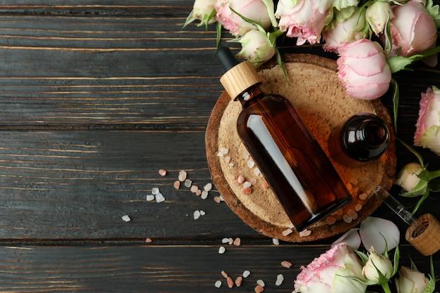 Концепция ухода за кожей с эфирным розовым маслом на деревянном столе