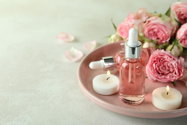 Skin care concept with essential rose oil on white textured table