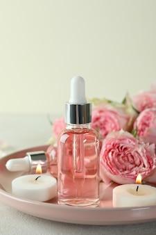 concetto di cura della pelle con olio essenziale di rose sul tavolo testurizzato bianco