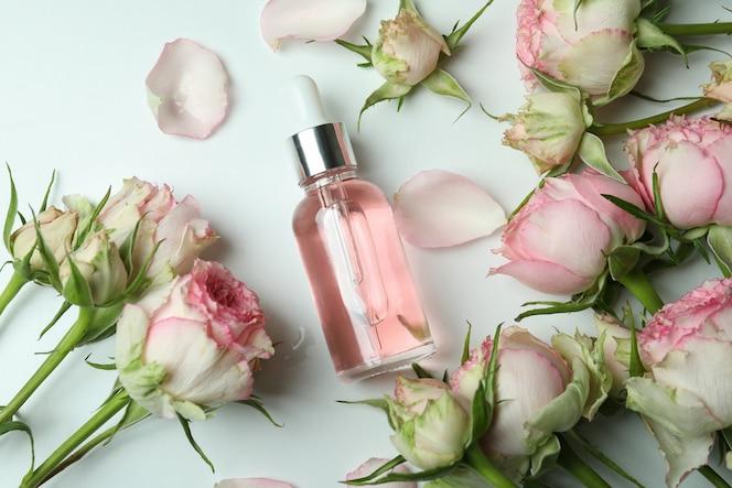 concetto di cura della pelle con olio essenziale di rose su bianco