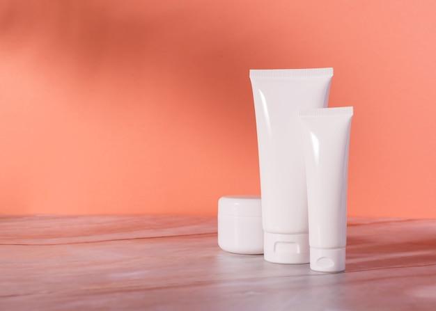 Бутылка косметики для ухода за кожей и банка с кремом на мраморном столе. упаковка натуральной косметики