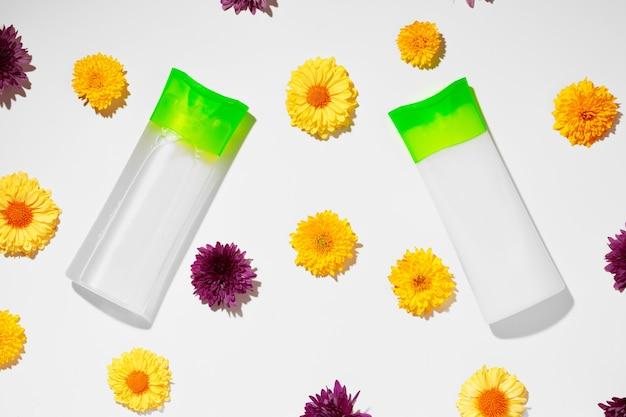 花の背景の上面図のスキンケア化粧品チューブ