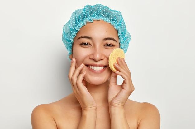 スキンケア、美容、フェイシャルトリートメントのコンセプト。美しい笑顔の女性は、スポンジで顔にファンデーションを塗り、入浴後の肌は滑らかで、シャワーキャップを着用し、白い壁にモデルを置きます