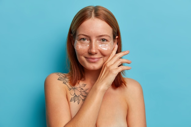 Skin care and cosmetology procedure. satisfied freckled woman touches face gently, wears hydrogel eye patches, stands naked, has perfect well cared body with charming smile.