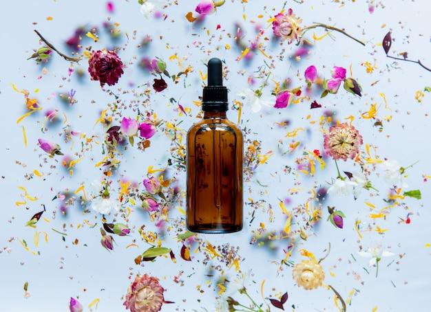 스킨 케어 크림 병 및 흰색 표면 주위에 마른 꽃