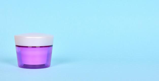 紫色の容器に入ったスキンケアクリーム。分離されました。