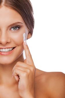 Уход за кожей. обрезанное изображение молодой женщины, намазывающей крем на лице и улыбающейся, стоя на белом фоне
