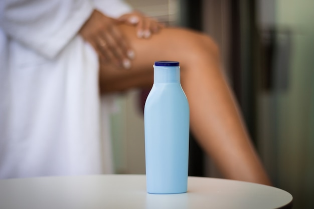Skin care during summer concept: close-up bottle of cream and woman applying body lotion o