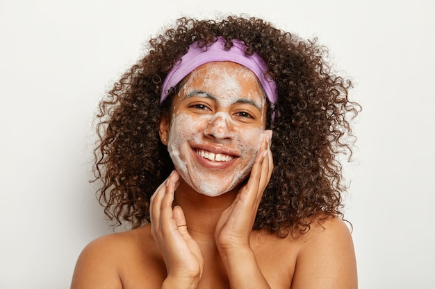 Skin care and ethnicity concept. beautiful satisfied curly woman washes face, has foam on skin, looks happily, stands topless against white wall, enjoys freshness and cleanliness