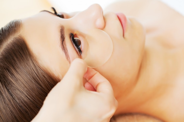 Skin care under the eyes, patches are applied to the young woman's eyes
