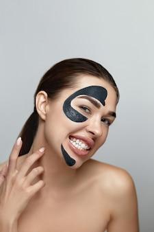 Уход за кожей лица, черная маска. портрет красоты привлекательных девушек с увлажняющей маской. красивая модельная девушка с косметической маской для лица курорта.