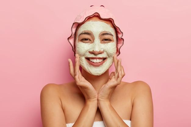 모든 연령대의 피부 관리. 얼굴에 클레이 마스크를 벗겨 낸 행복한 아시아 여성은 미용 치료를 받고 유쾌하게 보이고 뺨을 만지며 샤워 캡을 착용합니다.