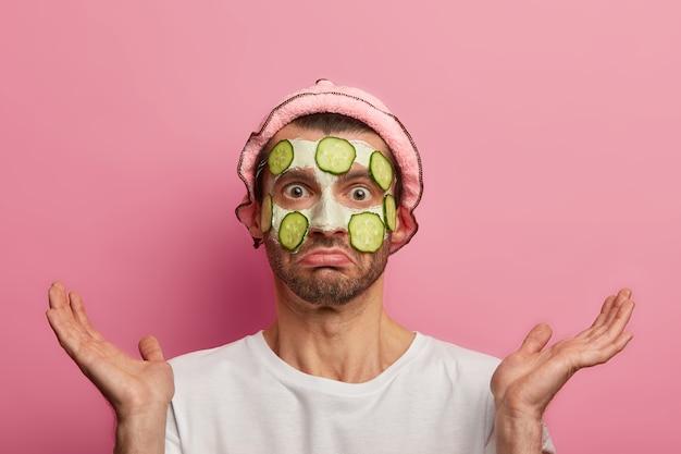 男性のスキンケア。恥ずかしい困惑した男は、キュウリのスライスで顔のマスクを適用し、にきびやにきびをきれいにし、手のひらを広げます
