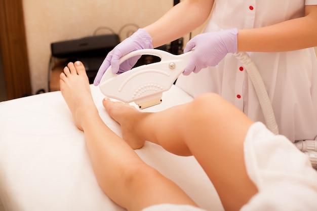 Уход за кожей. удаление волос на ногах, лазерная процедура в клинике. косметолог удаляет волосы на красивых женских ногах с помощью лазера