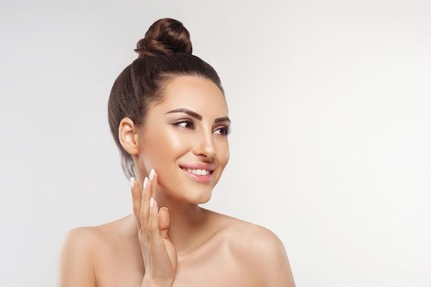 피부 관리. 행복 한 젊은 여자는 그녀의 얼굴에 크림을 적용. 화장품.