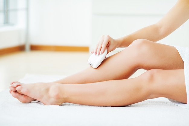 Skin care and health. hair removal. woman epilating leg, white electric epilator