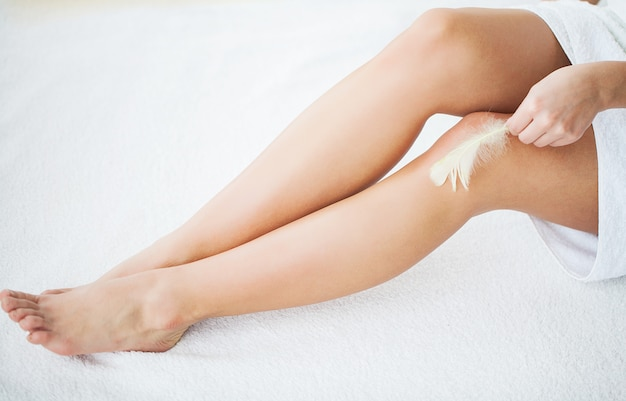 Skin care and health. hair removal. woman with feather touching bare legs on bed