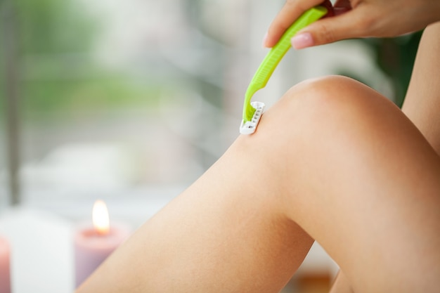 Skin care and health, women hair removal shaving legs with razor.