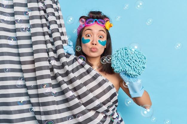 Skin care and hygiene concept. lovely asian woman keeps lips folded cleans body while showering holds soft sponge applies hair curlers hides behind curtain reduces wrinkles under eyes with patches