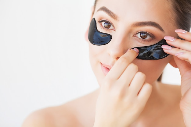 Skin care mask. woman with black patches