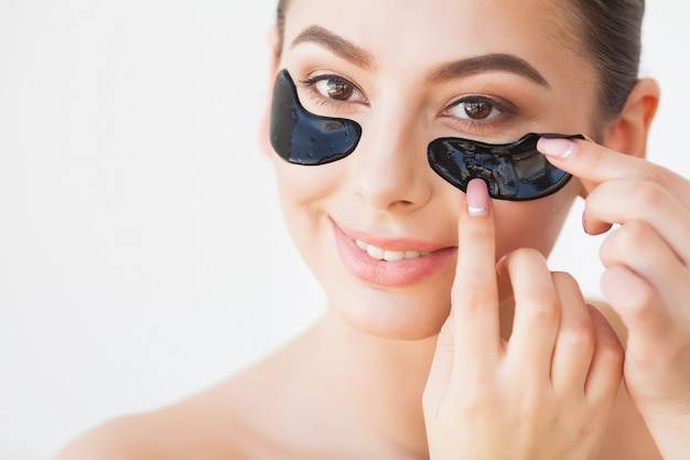 Skin care mask. woman with black patches.