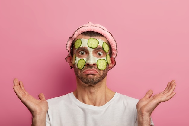 Skin care for men. embarrassed puzzled man applies facial mask with cucumber slices, cleans acnes and pimples, spreads palms